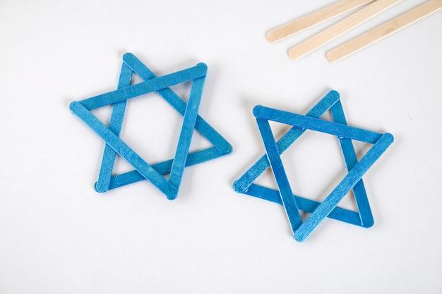 Diy. hanukkah decor. star of david from ice cream sticks on a white wooden table.