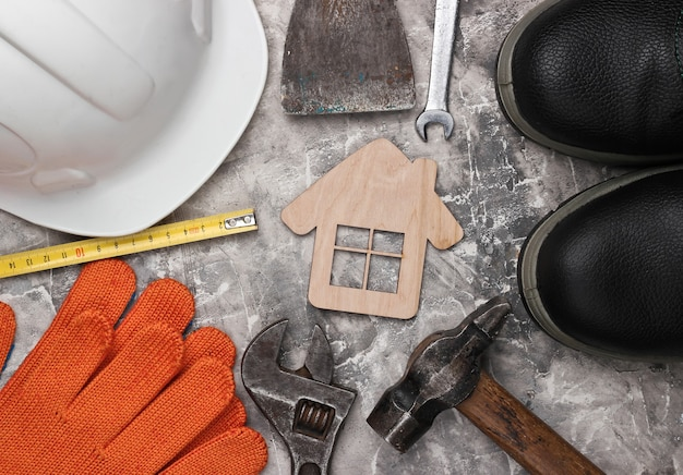 Diy home tool. construction tools and house figure on gray concrete background. flat lay composition. top view