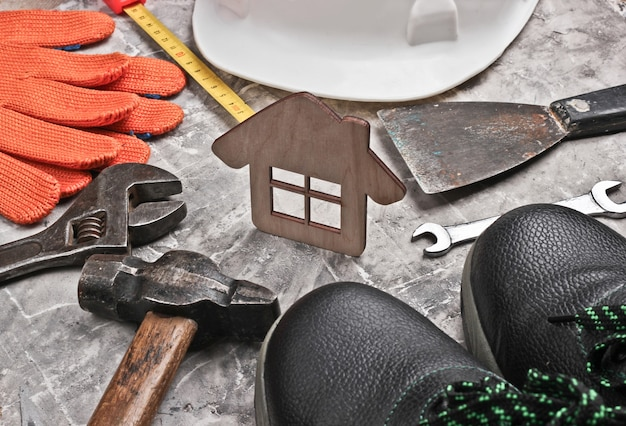 Diy home tool. construction tools and house figure on gray concrete background.