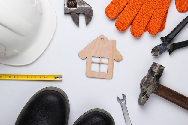 Diy home tool. construction tools and house figure on white background. flat lay composition. top view