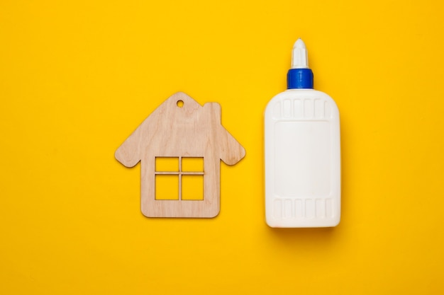Diy house concept. wooden mini house figurine and a bottle of glue on a yellow background. top view