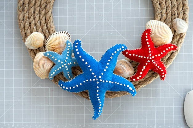 Diy instruction. step by step tutorial. making summer decor - wreath of rope with sea stars made of felt. craft tools and supplies. step 7 - final.