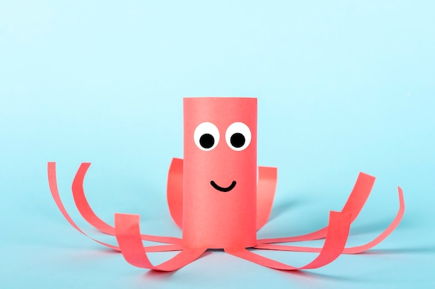 Diy and kids creativity. ecofriendly reuse recycle from toilet roll tube. children paper craft red octopus with tentacles.