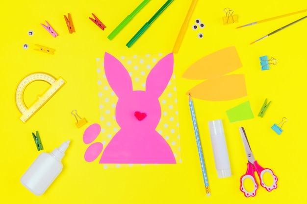 Diy and kids creativity. step by step instruction: create an easter card with bunny and carrot. childrens handmade easter craft. top view step 1