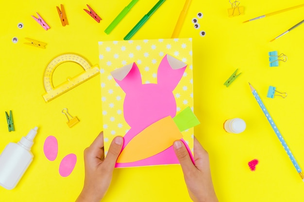 Diy and kids creativity. step by step instruction: create an easter card with bunny and carrot. childrens handmade easter craft. top view step 3
