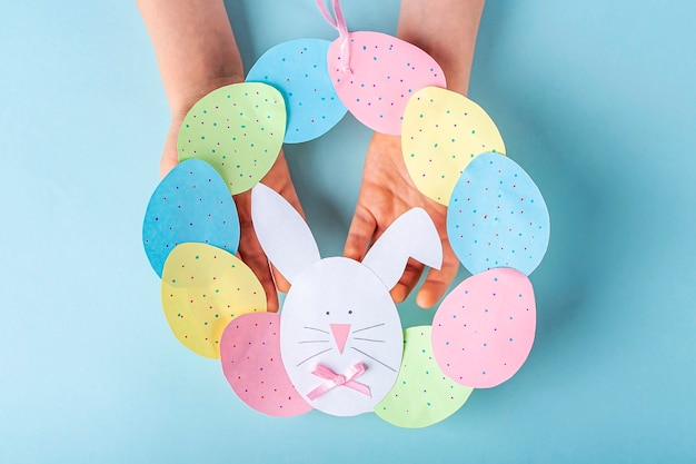Diy and kids creativity. step by step instruction: how to make paper easter wreath. step children's hands holding finished cute wreath of paper eggs and bunny. handmade easter craft