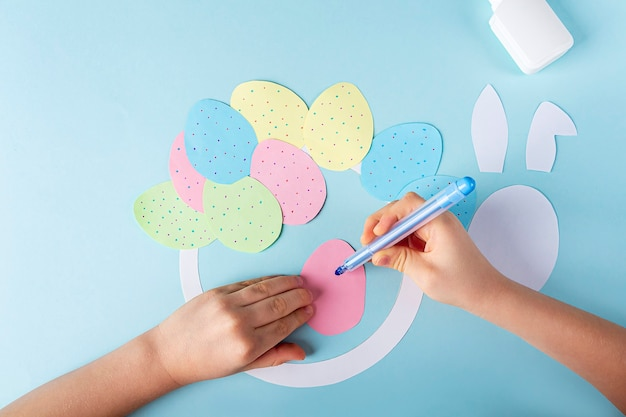 Diy and kids creativity. step by step instruction: how to make paper easter wreath. step decorate paper eggs with felt-tip pen. children's handmade easter craft.