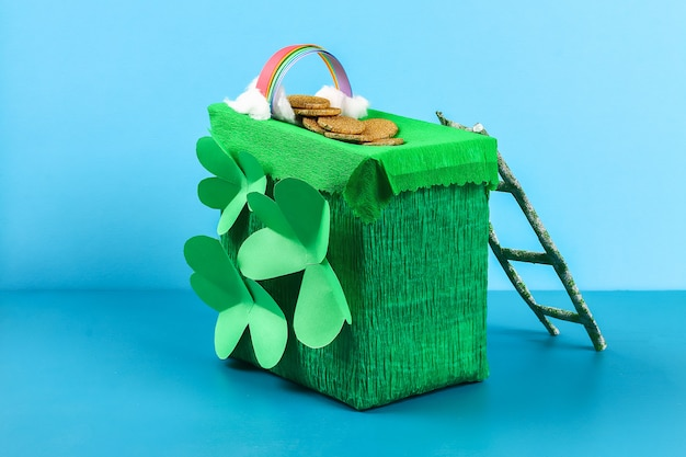 Diy leprechaun trap with gold coins, rainbow and green ladder st patricks day background.