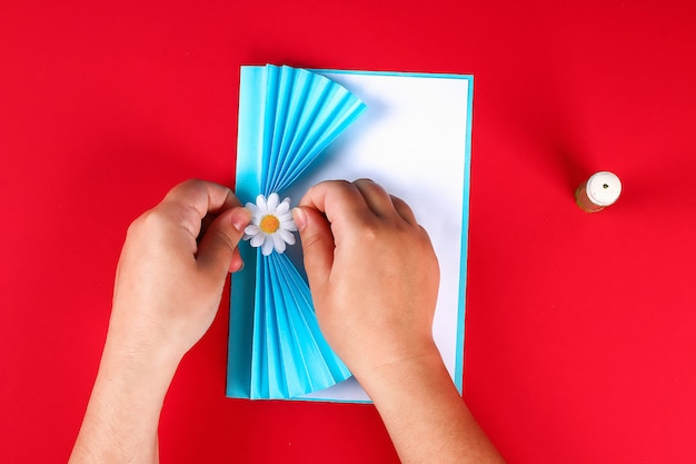 Diy mothers day greeting card in the form of curtain with paper chamomile flower on red background