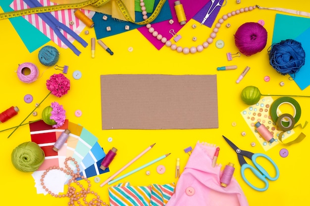 Diy. multicolored craft supplies and tool on yellow background. womens hobby -