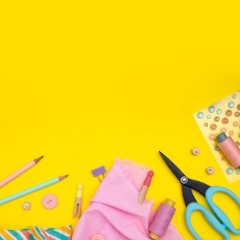 Diy. multicolored craft supplies and tool on yellow