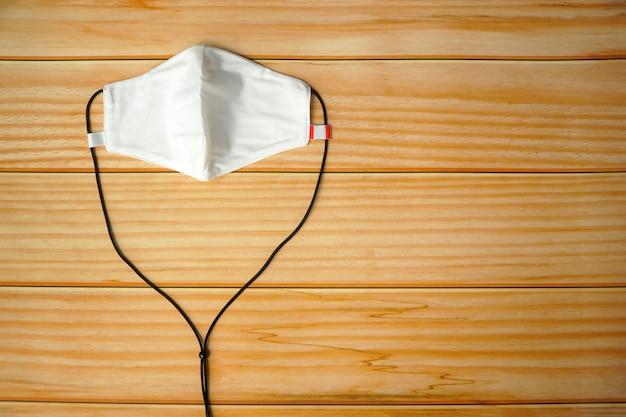 Взгляд сверху лицевого щитка гермошлема ткани diy белого на деревянной таблице. защитите слюну, кашель, пыль, загрязнения (pm 2,5), вирусы, бактерии, коронавирус. handmade, diy концепция. копировать пространство