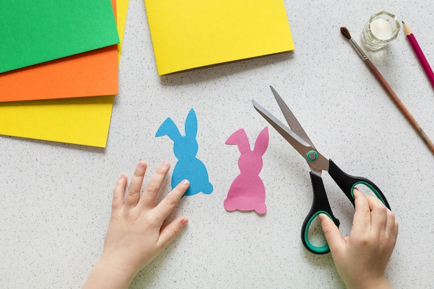 Diy postcard step by step. card happy easter with child hands. crafts concept for kids. step 3. cut out the rabbit, bunny.