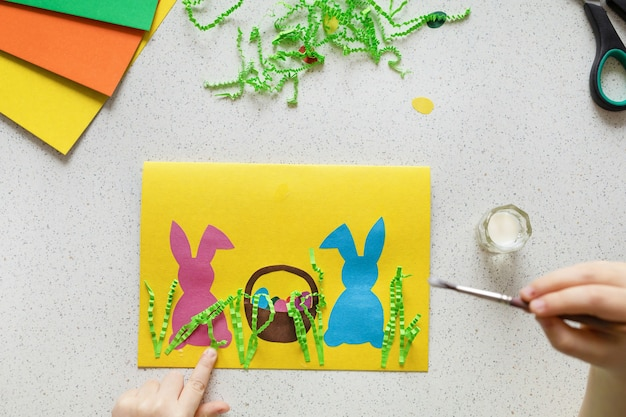 Diy postcard step by step. card happy easter with child hands. crafts concept for kids. step 8. glue the grass from the crumpled strips of paper on the cardboard.