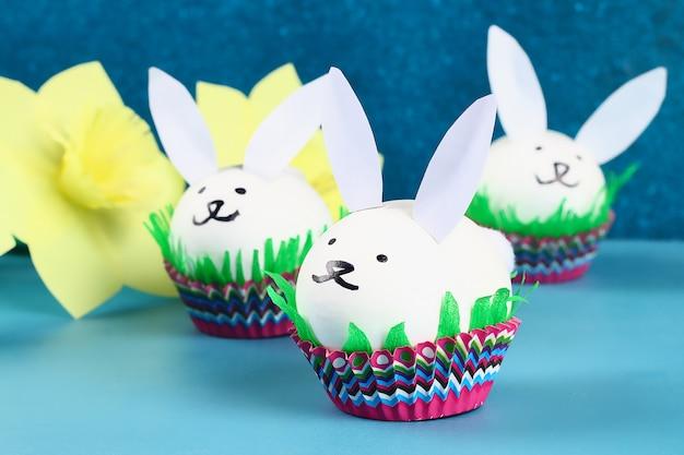 Diy rabbit from easter eggs on blue background. gift ideas, decor easter, spring. handmade.