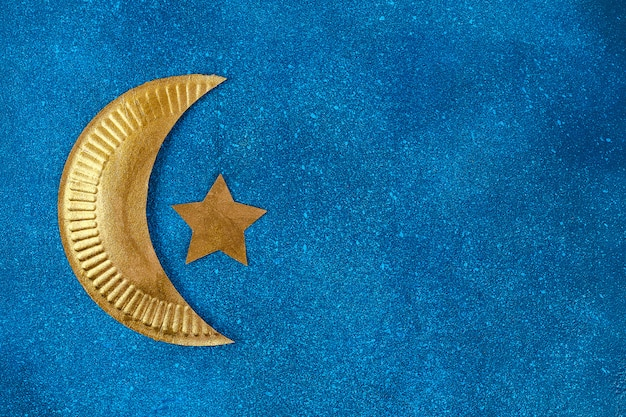 Diy ramadan kareem crescent moon with a star from a disposable cardboard plate and gold paint.