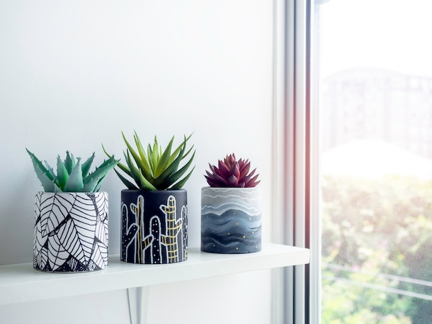 コピー スペースのあるガラス窓の近くの白い壁に白い木の棚に緑と赤の多肉植物を描いた diy の丸い形のコンクリート ポット。 3つのユニークなカラー塗装のセメントプランター。