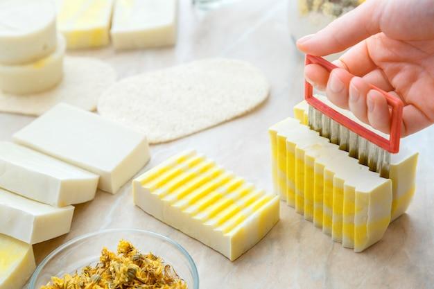 Процесс резки мыла своими руками. ремесленный процесс изготовления мыла с травами и цветами. хобби эко ремесленника мыло ручной работы на белом столе. множество различных бело-желтых домашних мыл.