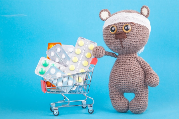 Diy toy. knitted brown bear cub. shopping for medicines, healthcare costs and prescription medication  with a shopping trolley filled with pills