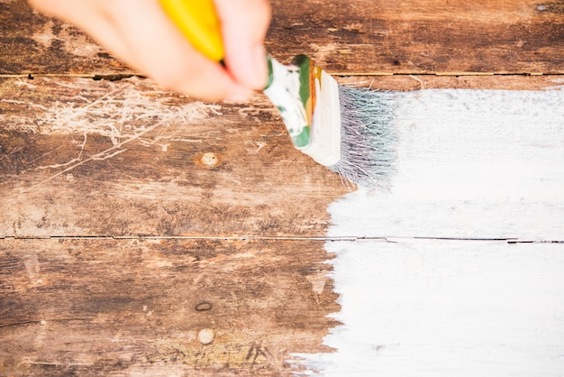 Diy woman hand using paintbrush decorating or painting old wood brown color to white color