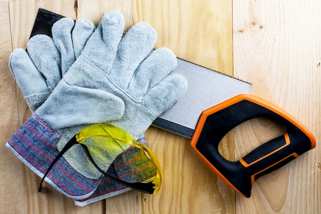 家の建設や修理に取り組みます。独立した更新、改修。のこぎり、作業用手袋、巻尺、ゴーグルを使用します。 diy、職場の安全、労働者保護のコンセプト