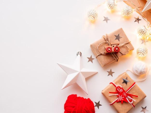 クリスマスと新年を包んだdiyプレゼントをクラフトペーパーに入れます。装飾としておもちゃの列車と素朴な糸で結ばれた贈り物。繊細なパターンの金属電球