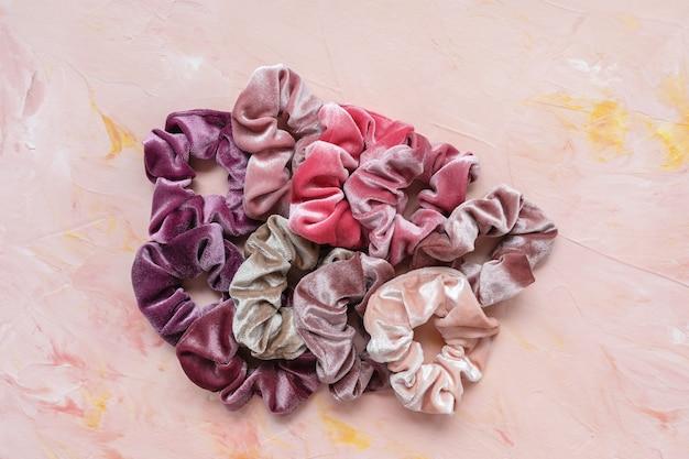 ピンクの背景のトレンディなベルベットのシュシュのコレクション。 diyのアクセサリーとヘアスタイルのコンセプト、コピースペース