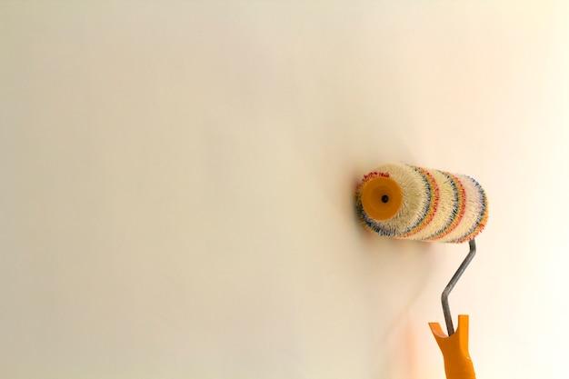 白い背景に分離された改装済みの部屋のインテリアの壁の近くのペイントローラーブラシ。改修とdiyのコンセプトです。