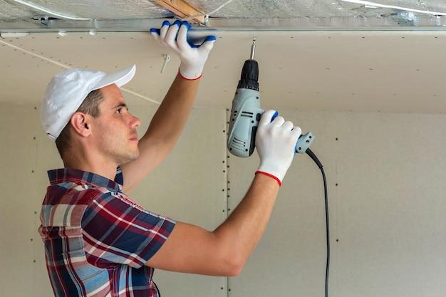 光沢のあるアルミ箔で絶縁された天井に電動ドライバーを使用して乾式壁吊り天井を金属フレームに固定する通常の服と作業用手袋の若い男。 diy、自分でやるコンセプト。