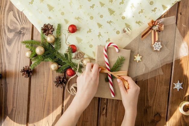 Руки женщины, упаковка рождественский подарок, крупным планом. неподготовленные рождественские подарки с элементами декора и предметов, вид сверху. рождество или новый год diy упаковки концепция.