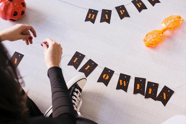 Взгляд сверху молодой женщины делает гирлянду хеллоуина. творческий diy. домашний декор проект партии. хэллоуин ремесло вдохновения.