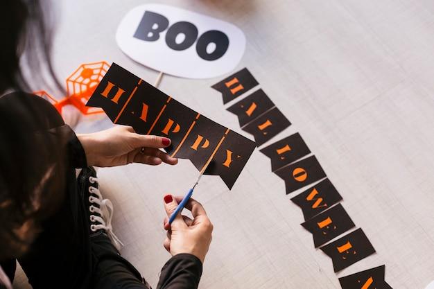 Молодая женщина делает хэллоуин гирлянды. творческий diy. домашний декор проект партии. хэллоуин ремесло вдохновения.