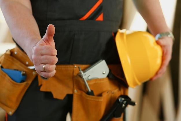 黄色いヘルメットショーの労働者の手は、腕の肖像画で親指でサインを確認します。手作業diyインスピレーション建具スタートアップアイデアフィックスショップハード帽子産業教育職業キャリアコンセプト