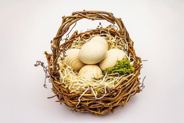 白い背景で隔離のイースターウィッカーバスケット。廃棄物ゼロ、diyコンセプト。木の卵、削りくず、苔