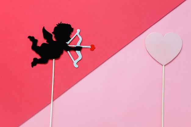 Diy фото стенд реквизит стрелка стрельбы амура в красное сердце на современные деревенские розовые обои в студии домашнего офиса.