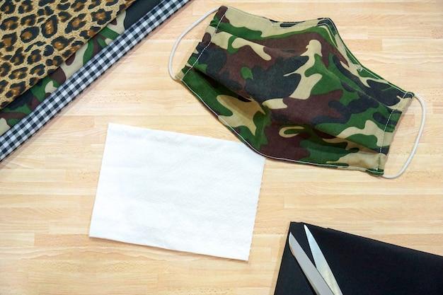 木のテーブルに綿、白いティッシュペーパー、diyミリタリー迷彩フェイスマスクを重ねる