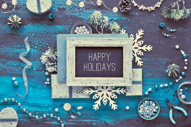 創造的なdiyクラフト趣味。クリスマスプレゼントとして手作りのジュエリーを作ります。装飾的な黒板にテキスト「幸せな休日」。暗い液体アートアクリルにフラットレイ