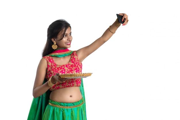 白のスマートフォンを使用して光ディワリ祭の間に粘土ランプまたはdiyaでselfieを取っている美しい若い幸せな女の子
