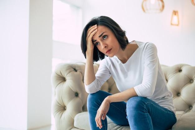 현기증. 현기증을 앓고있는 동안 소파에 앉아 이마를 잡고있는 여성의 측면 사진.