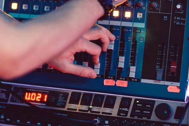 Dj adjusting audio mixing console
