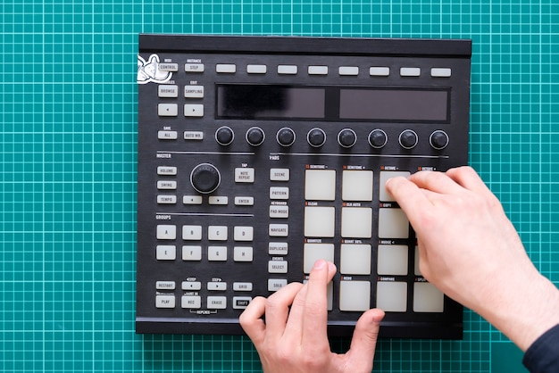 Dj audio producer fingers play the drum music on pads of drum machine