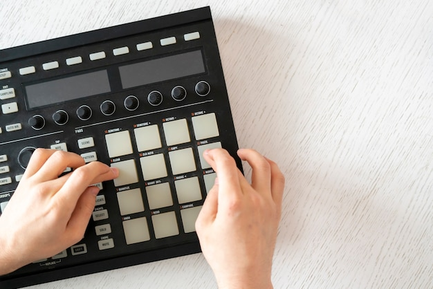 A dj audio producer fingers play the drum music on pads of drum machine