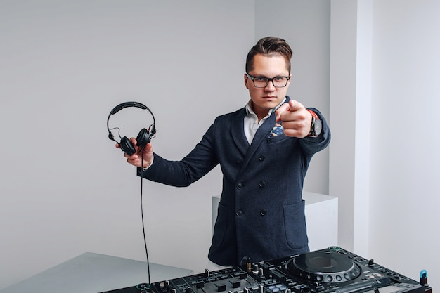 Dj in blue suit with mixer and headphones shows in camera