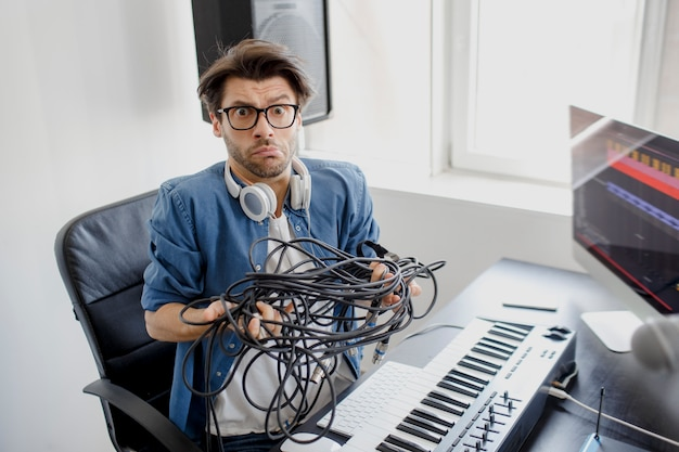 Dj in broadcasting studio with cables