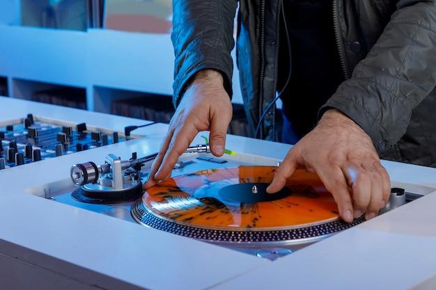 Dj colocando disco de vinil en tocadiscos para reproducirlo concepto de musica retro