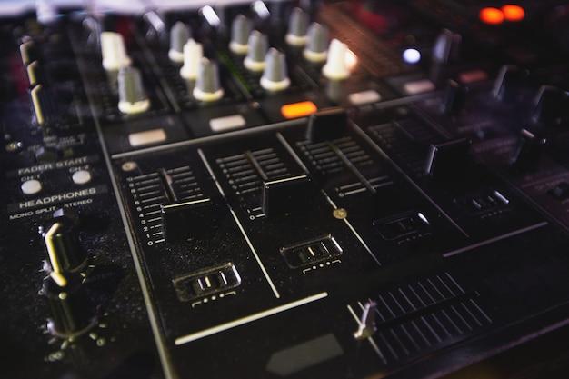 音楽をミキシングするためのdjコンソール。閉じる。プロの音楽機器。技術と最新技術。 djの仕事。ナイトライフのコンセプト。良い音楽でパーティーを絶賛してください。