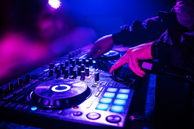 手と夜のクラブパーティーで踊るぼやけた人々と音楽をミキシングするためのdjコンソール