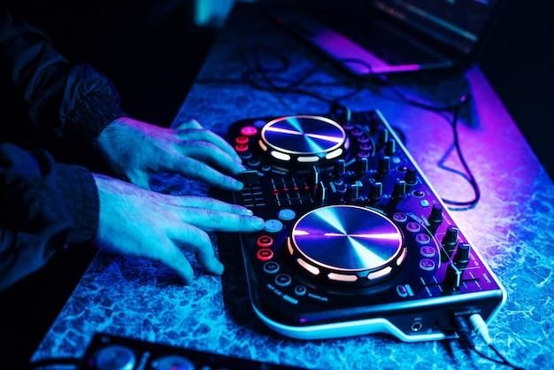 손으로 음악을 믹싱하고 나이트 클럽 파티에서 흐릿한 사람들이 춤을 추는 dj 콘솔