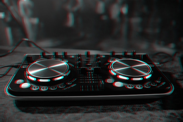 Dj console for mixing music with blurry people dancing at a nightclub party.