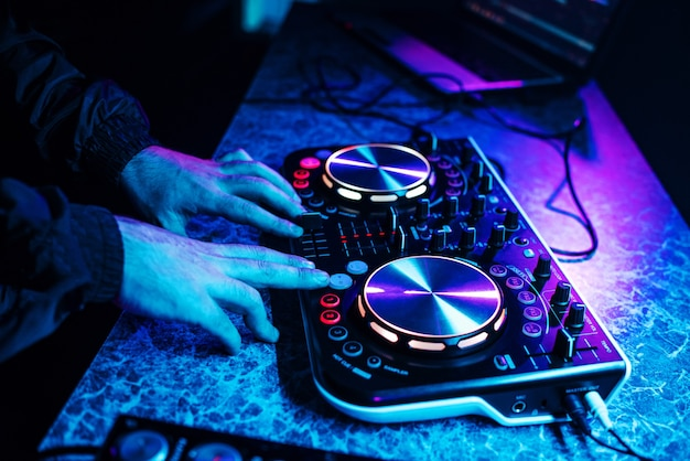 Dj console for mixing music with hands and with blurred people dancing at a night club party